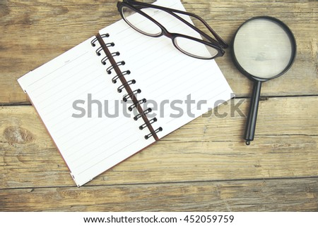 magnifier,glasses and notebook on wooden table - stock photo