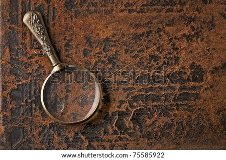 Magnifier on background cover of ancient book - stock photo