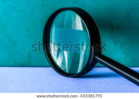 Magnifier on blue background close up - stock photo