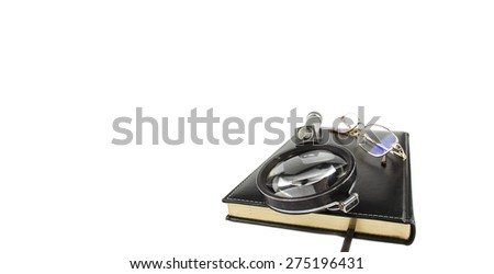 Magnifier with the glasses on the book - stock photo