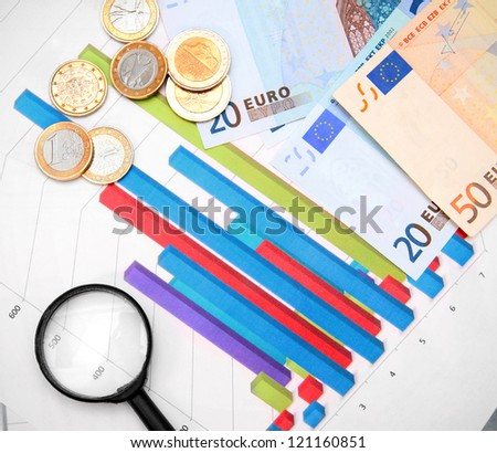 Magnifiers and euro money on graphs. - stock photo