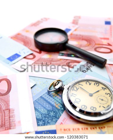 Magnifiers and watch on the money. - stock photo