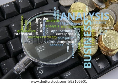 Magnify glass and coins on keyboard. Business analysis concept on cloud words.