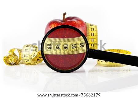 Magnifying glas and red apple wrapped with the meter, on a white background. - stock photo