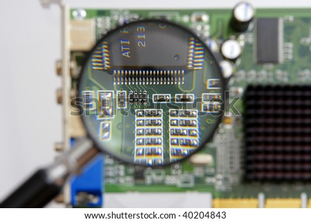 magnifying glass above a circuit board - stock photo