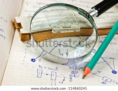 magnifying glass and a slide rule on the old page with the calculations in mechanics - stock photo