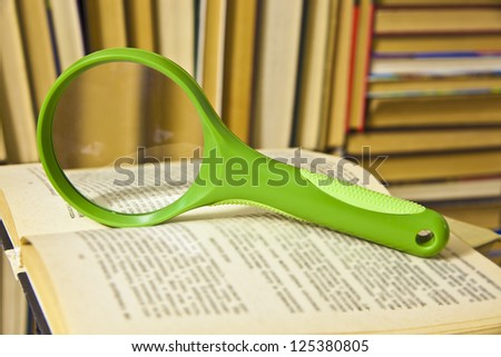magnifying glass and an open book on a table - stock photo