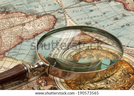 Magnifying glass and ancient old map - stock photo