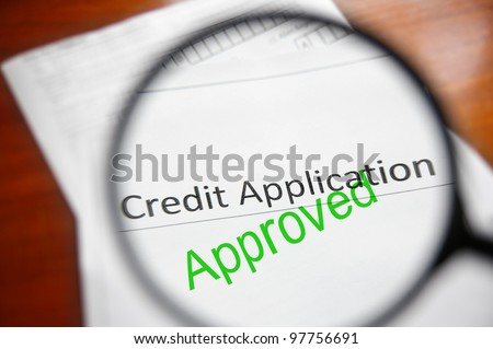 magnifying glass and approved credit application form - stock photo