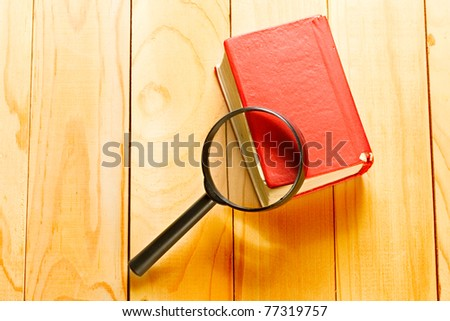 Magnifying glass and book o the wooden background - stock photo