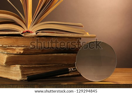 Magnifying glass and books on table - stock photo