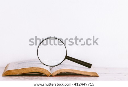 Magnifying glass and books on wooden table - stock photo