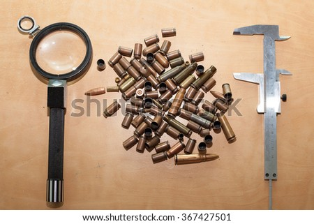 magnifying glass and bullets. investigation of the crime. - stock photo