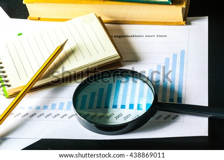 Magnifying glass and business growth graph - stock photo