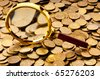 Magnifying glass and coins at the background - stock photo