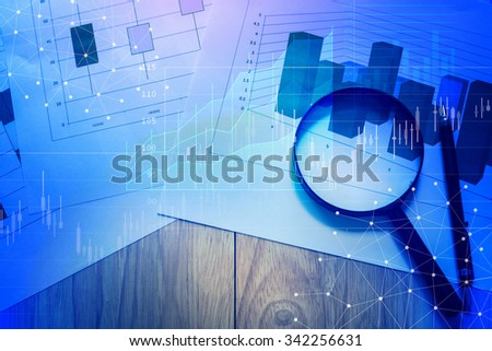 Magnifying glass and documents with analytics data lying on table,selective focus - stock photo