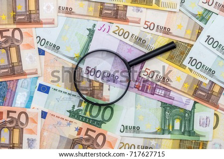 magnifying glass and euro banknotes, euro coin