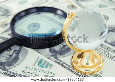 magnifying glass and globe on dollars background - stock photo