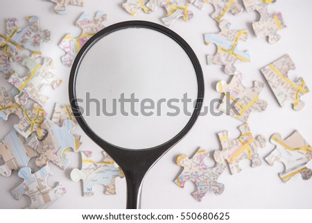 Magnifying glass and jigsaw puzzle on office table