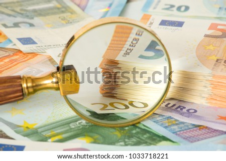 Magnifying glass and many euro bills