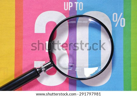 magnifying glass and newspaper advertising 30%. - stock photo