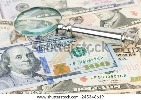 Magnifying glass and one hundred dollar bank note