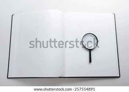 Magnifying glass and open book. Search information. Copy space - stock photo
