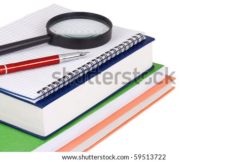 magnifying glass and pen on books
