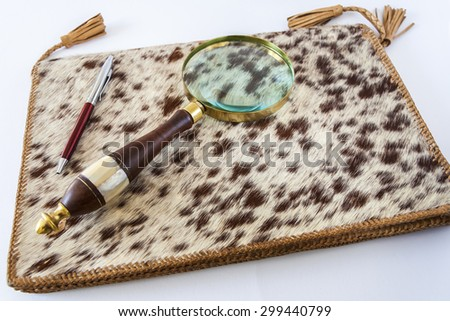 Magnifying Glass And  Pen On Leather Folder - stock photo