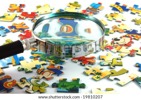 magnifying glass and puzzle - stock photo