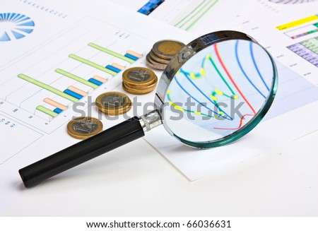 magnifying glass and the working paper with coinss