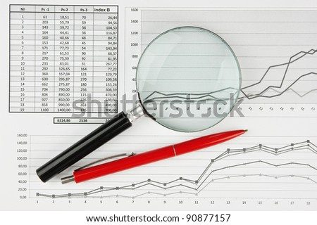 magnifying glass and working paper with  diagram - stock photo