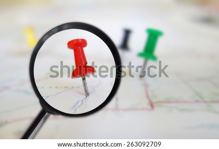 Magnifying glass closeup of push pin tacks in a map                                - stock photo