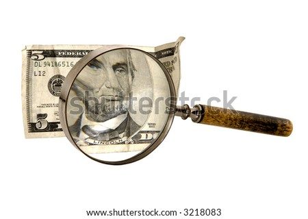 magnifying glass enlarging portion of US five dollar bill on white background - stock photo