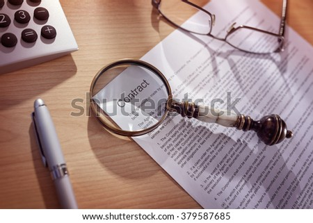 Magnifying glass examining and signing a legal contract document - stock photo