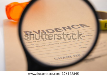 magnifying glass focus on evidence bag for detective and law enforcement - stock photo