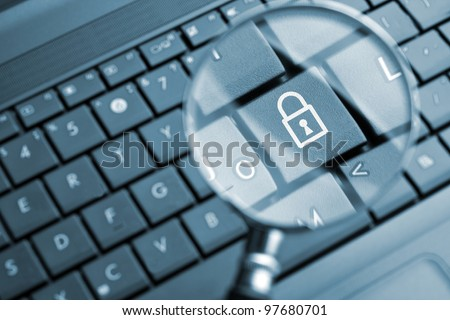 Magnifying glass focused on lock icon - stock photo