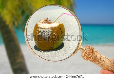Magnifying glass focusing on a coconut tropical drink on the beach oceanside - stock photo
