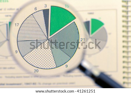 Magnifying glass focusing on a diagram. - stock photo