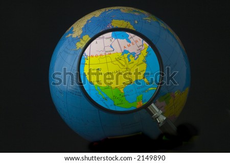 Magnifying glass focusing on North America - stock photo