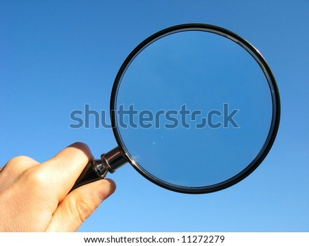 MAGNIFYING GLASS - Hand holding a magnifying glass. - stock photo