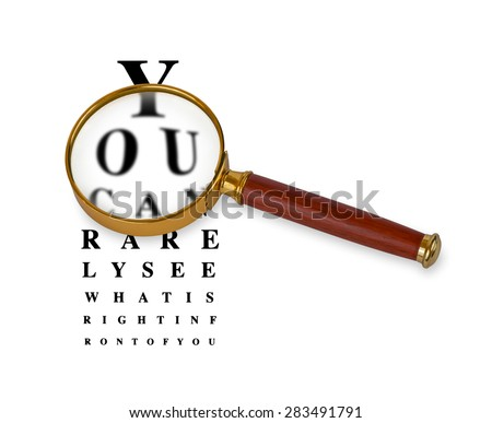 Magnifying glass in front of a funny eyetest chart. Eyetest in background is sharp while vision through magnifying glass lens is blurred. Magnifying glass has golden rim and wooden handle.  - stock photo