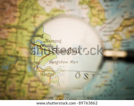 Magnifying Glass in front of a Shanghai map - stock photo