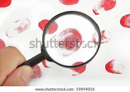 Magnifying glass in hand and fingerprints on white background - stock photo