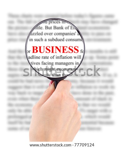 Magnifying glass in hand and word busines - stock photo