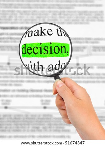 Magnifying glass in hand and word Decision - business background - stock photo