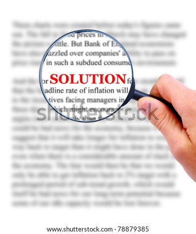 Magnifying glass in hand and word solution - stock photo
