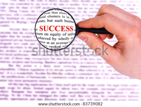 Magnifying glass in hand and word success - stock photo