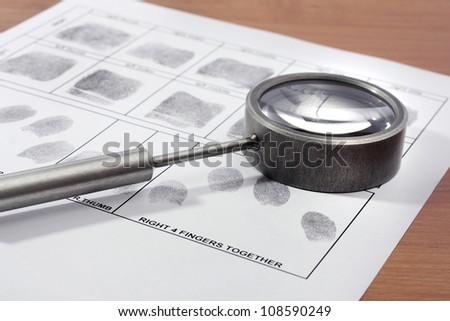 Magnifying glass inspecting a fingerprint. - stock photo