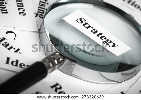 Magnifying glass is focusing on the strategy word with lot of other business concept words around.